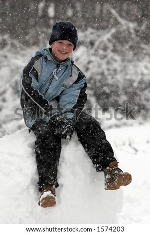 Kid sitting on a snowball - stock photo