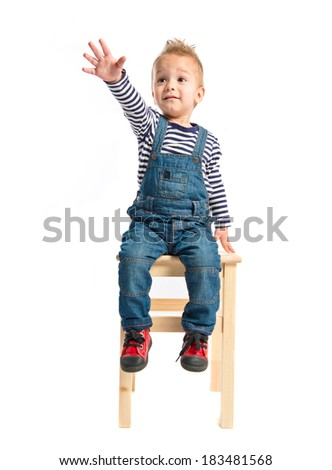 Kid sitting on a wooden chair over white background