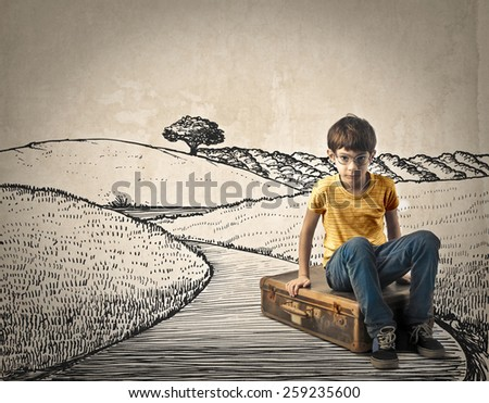 Kid sitting on his suitcase  - stock photo