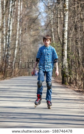 Kid skating on rollerblades in spring park - stock photo