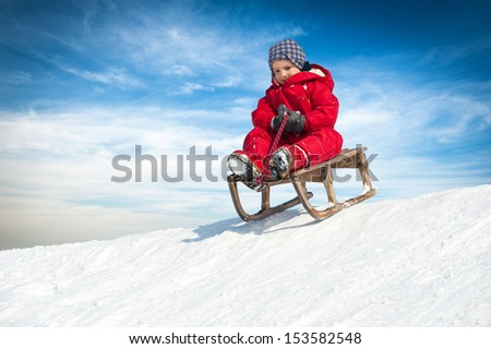 Kid sliding with sledge in the snow.