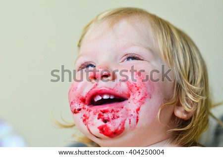 Kid smiling and having fun eating. Cute little girl with blonde hair having fun after spilling a cup of smoothie and smearing her face. Weekend, warm and cozy scene in the kitchen. - stock photo