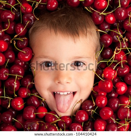 Kid smiling face portrait surrounded by cherries. - stock photo