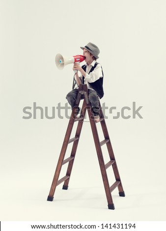 Kid speaking with megaphone on top of a ladder - stock photo