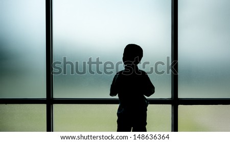 Kid standing and looking out through the window - stock photo