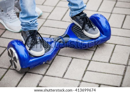 Kid standing on a modern blue electric mini hover board scooter outdoors. Popular new city transport that is easy and fun to ride and makes no air pollution to the atmosphere  - stock photo