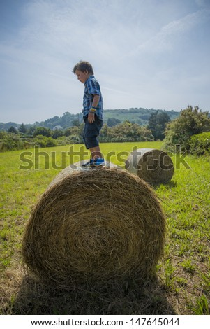 kid standing on a round hay bale,looks like he's balancing on it - stock photo