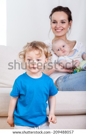 Kid standing with mother and baby in the background