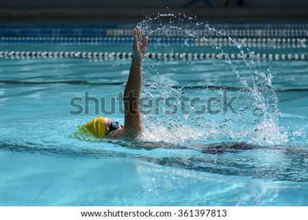 Kid swimmer swimming on pool with backstroke stroke for race
