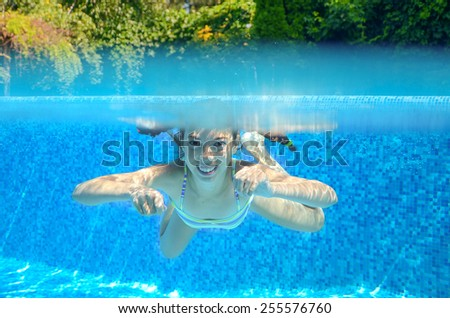 Kid swims in pool underwater, girl swimming, playing and having fun, children water sport