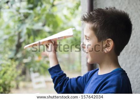Kid throws paper plane. Authentic image - stock photo