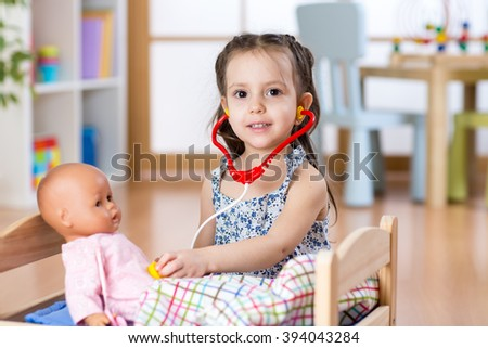 Kid toddler playing doctor role game examining her doll using stethoscope sitting in playroom at home, school or kindergarten - stock photo