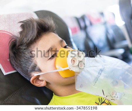 Kid traveling by airplane with need for oxygen first emergency aid - stock photo