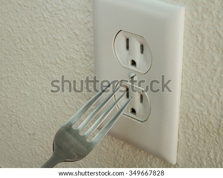 Kid trying to put a metal fork into an electrical outlet - stock photo
