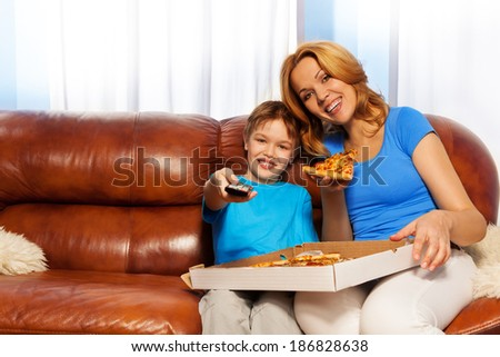 Kid TV channel and mother eating pizza - stock photo