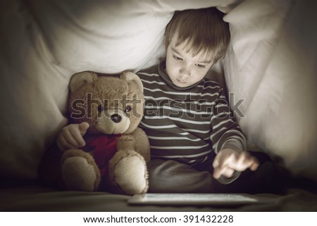 Kid under the blanket playing with tablet - stock photo