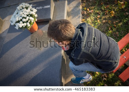 Kid visiting graves at cemetery