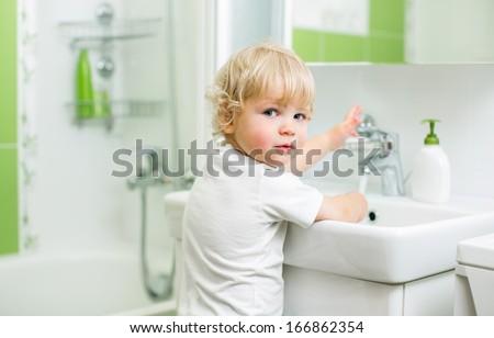 kid washing hands in bathroom - stock photo