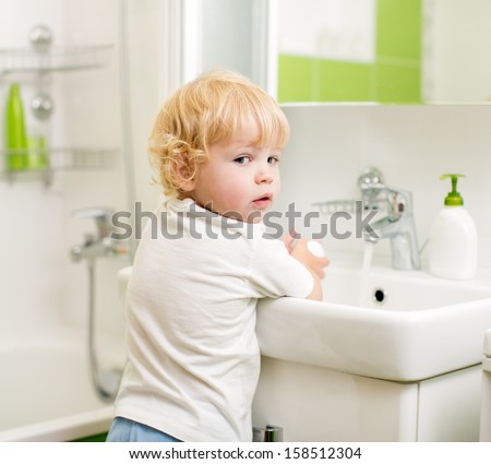 kid washing hands with soap in bathroom - stock photo