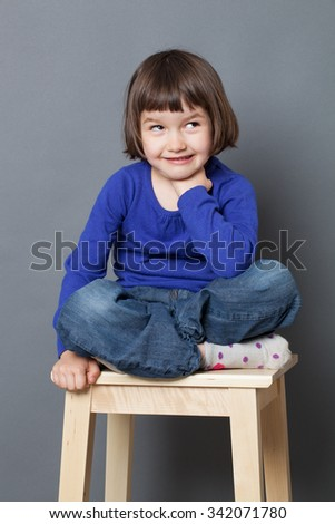kid wellbeing concept - cheeky preschool child sitting in relaxing crossed legs position expressing healthy childhood,studio shot - stock photo