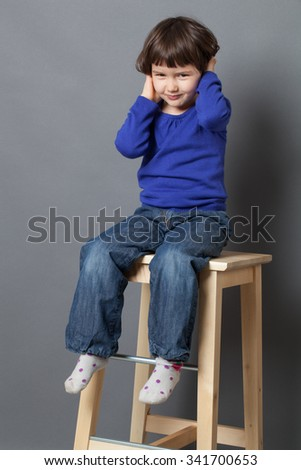 kid wellbeing concept - thrilled preschool child looking down in sitting on high wooden stool for happiness and wellbeing,studio shot