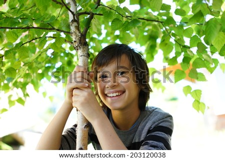 Kid with a tree in garden - stock photo