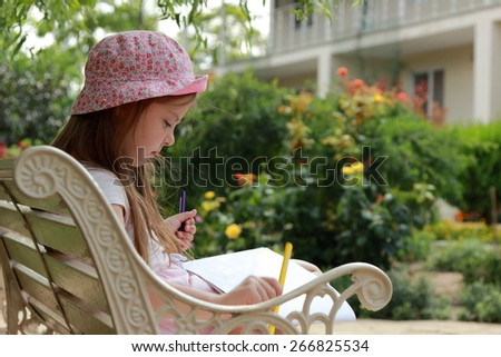 Kid with enthusiasm draws in album sitting in the summer park bench - stock photo