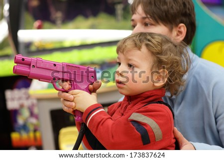 Kid with handgun at an amusement park - stock photo