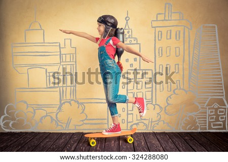 Kid with jet pack riding on skateboard. Child playing at home. Success, leader and winner concept - stock photo