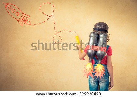 Kid with jetpack draw sketch on wall. Child playing at home. Success, leader and winner concept - stock photo