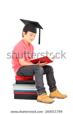Kid with mortarboard reading a book seated on a stack of books isolated on white background - stock photo