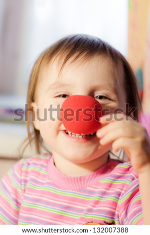 Kid with red nose clown fooling around.