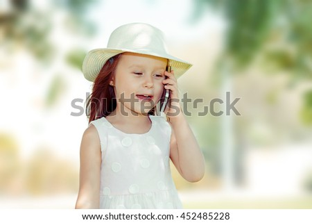 Kid with smartphone. Closeup portrait of pretty smiling funny girl kid holding cell phone  talking to her mom, dad family isolated green trees outdoors summer background. Kids and technology concept - stock photo