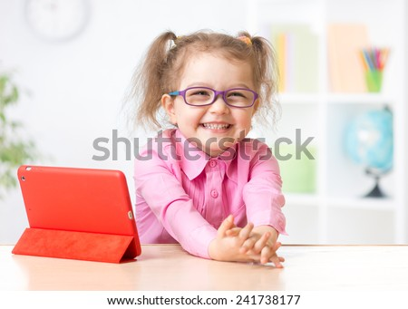 kid with tablet in glasses as early education concept