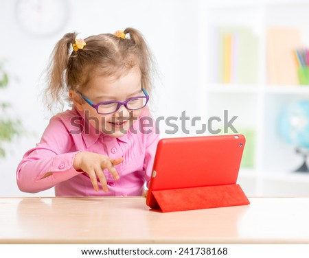 Kid with tablet PC in glasses learning with great interest - stock photo
