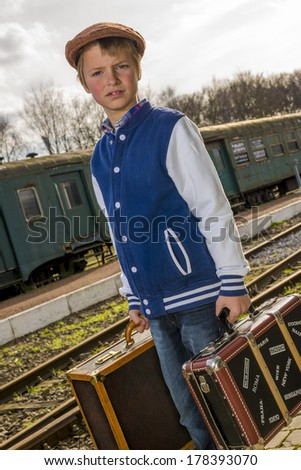 kid with vintage suitcases waiting on his train to arrive - stock photo