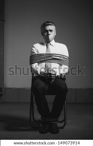 Kidnapped businessman. Black and white image of tied up businessman sitting at the chair and looking at camera - stock photo