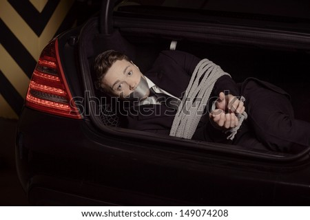 Kidnapped businessman. Tied up young men lying in the car trunk and looking at camera - stock photo
