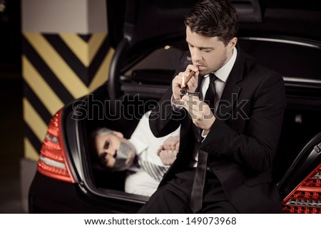 Kidnapped man. Tied up businessman lying in the car trunk and looking at camera while kidnapper smoking a cigar - stock photo