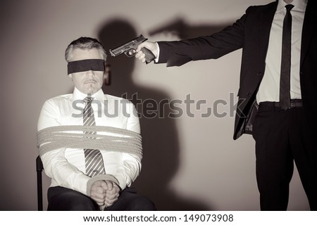 Kidnapper and victim. Tied up businessman sitting at the chair while young man in formalwear aiming him with gun - stock photo
