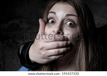 Kidnapping. Terrified young woman with hand covering her mouth staring at camera