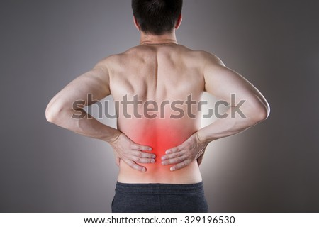 Kidney pain. Man with backache. Pain in the man's body on a gray background with red dot - stock photo