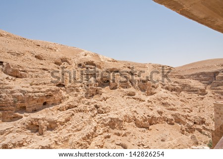 Kidron river strata canyon panorama with monastic cave-cells in the mountain wall viewed from terrace of The Great Lavra of St. Sabbas the Sanctified (Mar Saba) in Judean desert. Palestine, Israel.