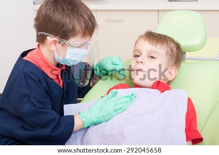 Kids acting as doctor and patient in dental office. Fearless boy patient concept