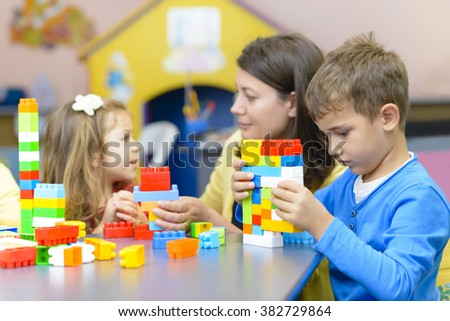 Kids and educator playing with plastic building blocks at kindergarten - stock photo