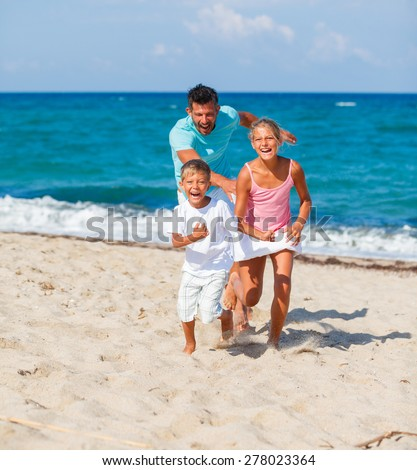 Kids and father playing together on the tropical beach. - stock photo