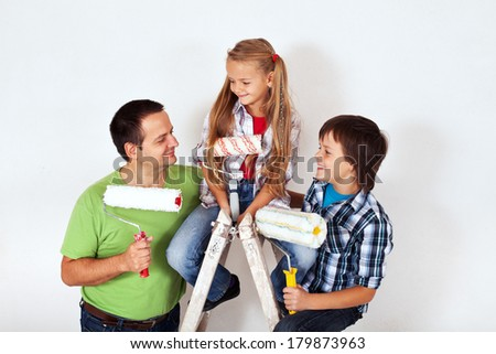 Kids and father with paint rollers and painting ladder - smiling happily