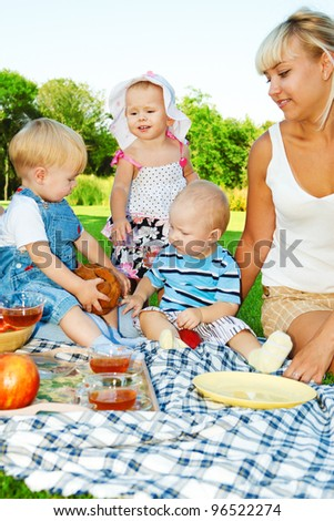Kids and mothers enjoying picnic in the backyard - stock photo