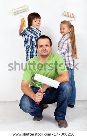 Kids and their father painting a room - holding paint rollers - stock photo