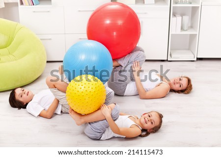 Kids and their mother exercising at home using large gymnastic balls